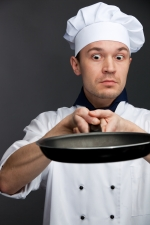 supsised chef holding frying pan isolated on grey background